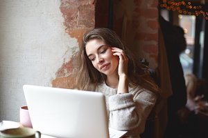 Beautiful gorgeous young brunette lady in cozy sweater using laptop