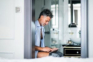Mature businessman with tablet in a hotel room bathroom.