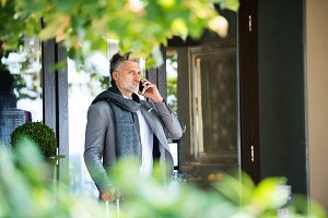 Mature businessman with smartphone in front of a hotel.