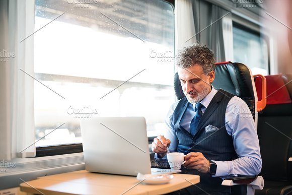 Mature businessman with laptop travelling by train. in Graphics