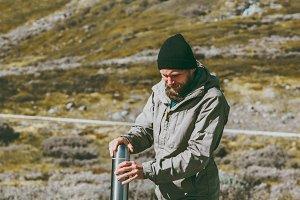 Man traveler holding thermos