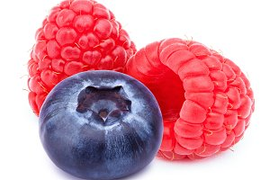 Two raspberries and one blueberry isolated
