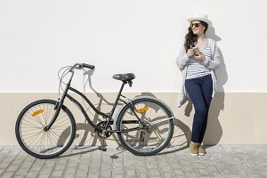 Young woman with gadget and bike