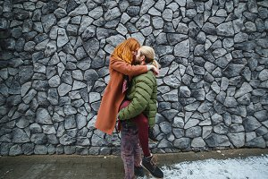 Happy young couple enjoying life. Young stylish couple embrace at grey wall urban background.