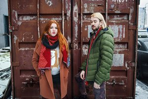 People winter fashion concept. Stylish couple at shipping container. Man clothed in green jacket, red scarf and jeans. Woman clothed in brown coat, shorts and red scarf