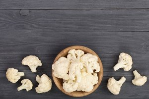 Fresh cauliflower cut into small pieces in wooden bowl on black background with copy space for your text. Top view