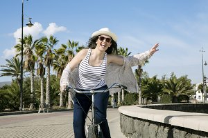 Young happy woman cycling in Spain