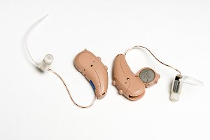 Close up of a pair of tiny modern hearing aids on white background