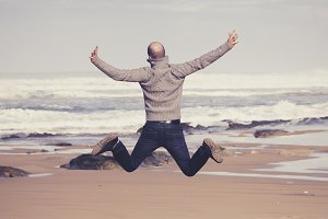 Happy man jumping in the beach