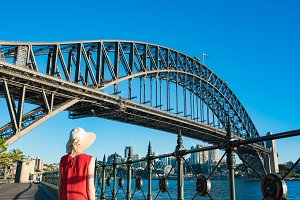 Woman in bright top and hat against Sydney Harbour Bridge on the background