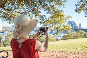Woman sitting on a bench and looking at Sydney Harbour