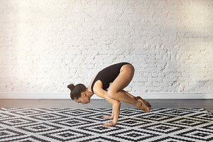 Young asian woman in the Bakasana (Crane) yoga pose