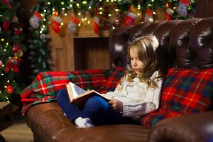 Happy little girl reading a story book by on the couch in a cozy