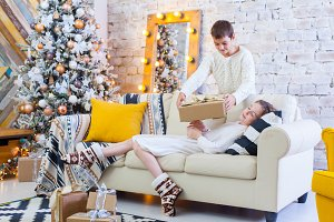 Two children a boy and a girl at a Christmas tree on a sofa with gifts. In light colors. give presents to each other
