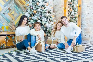 Family celebrating at home. father, mother and children on the background of the Christmas tree with presents sit on the carpet. New Year and xmas people.