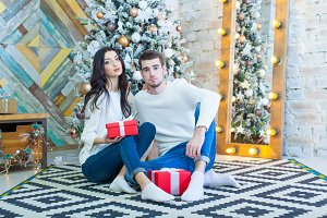 Young beautiful couple sitting near Christmas tree with xmas giftsin red boxe.