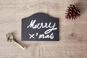 merry christmas text sign with pine cone and key ornament on rustic wooden