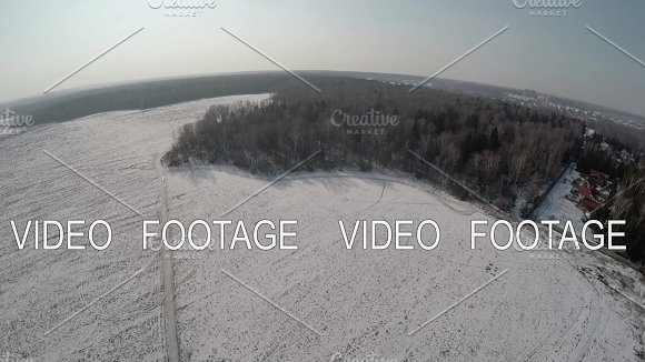Village with vast snowy fields near the forest, aerial view