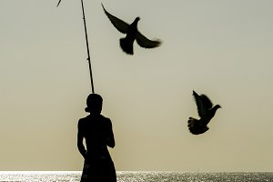 Silhouette of woman with fishing tackle