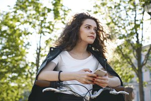 Attractive teenage girl leaning elbows on bicycle handlebars and holding cell phone