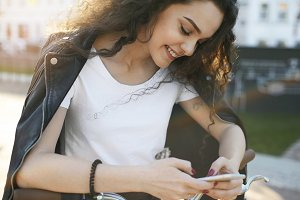 Cropped outdoor shot of pretty girl reading romantic text message from her boyfriend