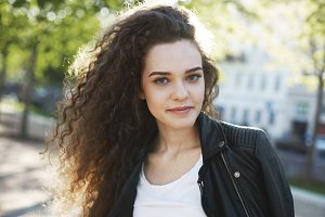 Portrait of beautiful young woman with long curly dark hair