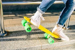 Pretty sporty girl with skateboard.