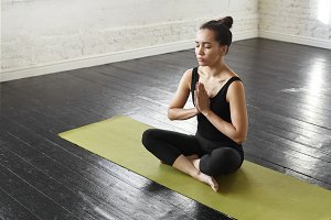 Portrait of pretty asian young businesswoman sitting in Prayer pose holding hands in namaste