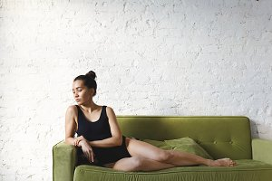 Attractive mixed race female model looks aside lies on a green sofa at home