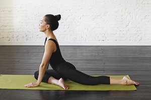 Attractive asian young woman practicing yoga pose Eka Pada Radjakapotasana