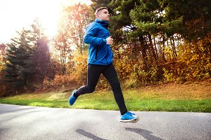 Young athlete running in park in colorful autumn nature.