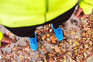 Young runner in autumn park standing on concrete path.