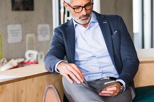 Mature businessman with smartphone in the office.