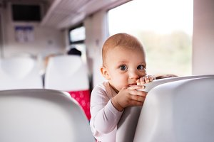 Cute baby boy travelling by train.