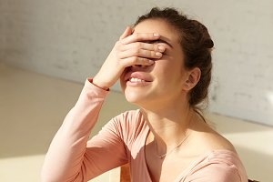 Attractive girl with cute smile covers face by hand squinting eyes in bright sun