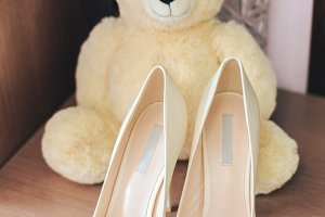 Shoes white bride with teddy bear, wedding attributes close-up, waiting for the wedding