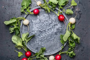 Radishes with leaves around plate