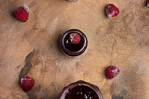 Raspberry jam on grunge background of concrete in vintage rustic style top view flat lying