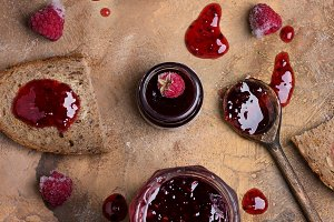 Raspberry jam with toast on grunge background of concrete in vintage rustic style top view flat to lie