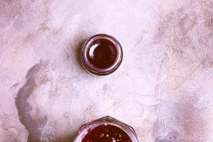 Raspberry jam  on grunge background of concrete in vintage rustic style top view flat to lie