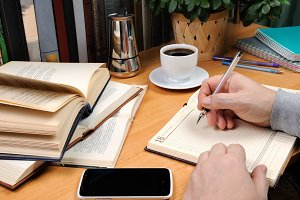 A man takes notes in a notebook
