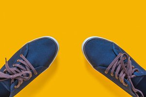 Blue sneakers on yellow background