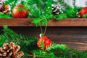 Red Christmas balls and cones lie on a wooden brown shelf surrounded by fir branches.