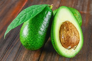 Three green raw ripe avocado fruits and a cut half with a bone with leaves on a brown wooden table.