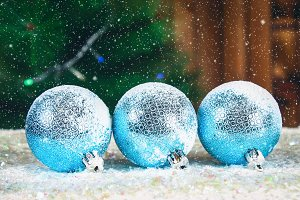 Three blue New Year balls on the snow. Christmas atmosphere.