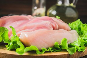 Raw chicken fillet and green salad on a round cutting board on a wooden table background. Meat ingredients for cooking.