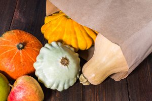 Autumn nature concept. Fall pumpkins and apples on wooden rustic table. Thanksgiving dinner.
