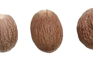 Three nutmeg whole isolated on white background. Top view