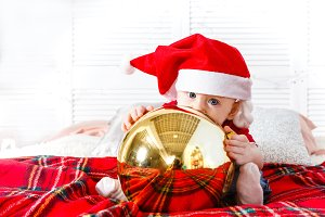 Baby with blue eyes in Santa hat