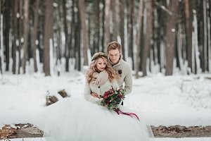 Bride and groom are sitting on the log in the winter forest. Close-up. Winter wedding ceremony.